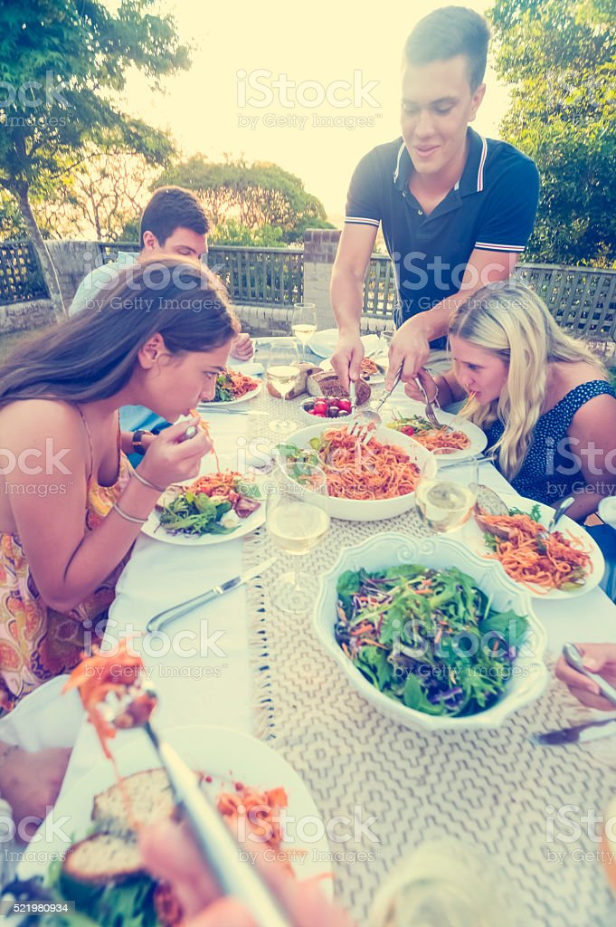 Group of friends having a meal outdoors stock photo
