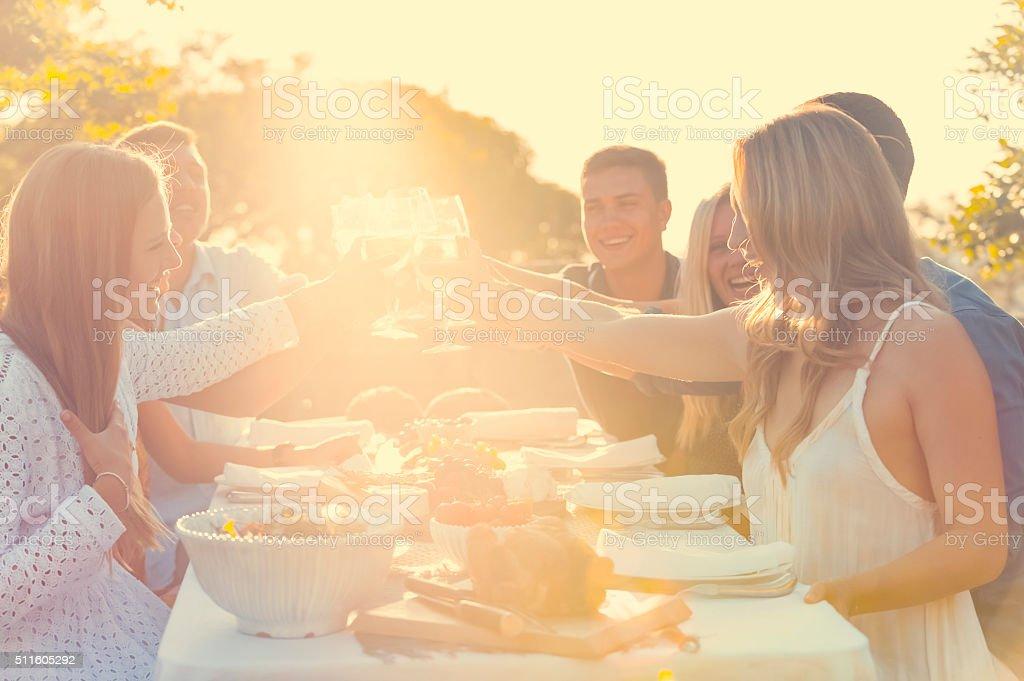 Groupe d'amis d'avoir boissons au coucher du soleil. - Photo
