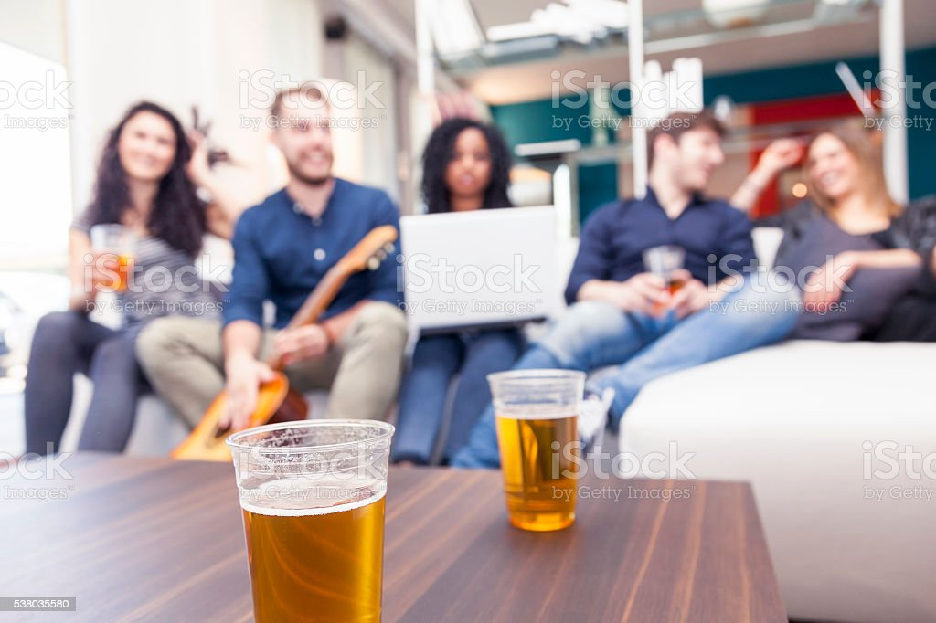 group of friends having fun drinking beer and playing guitar stock photo