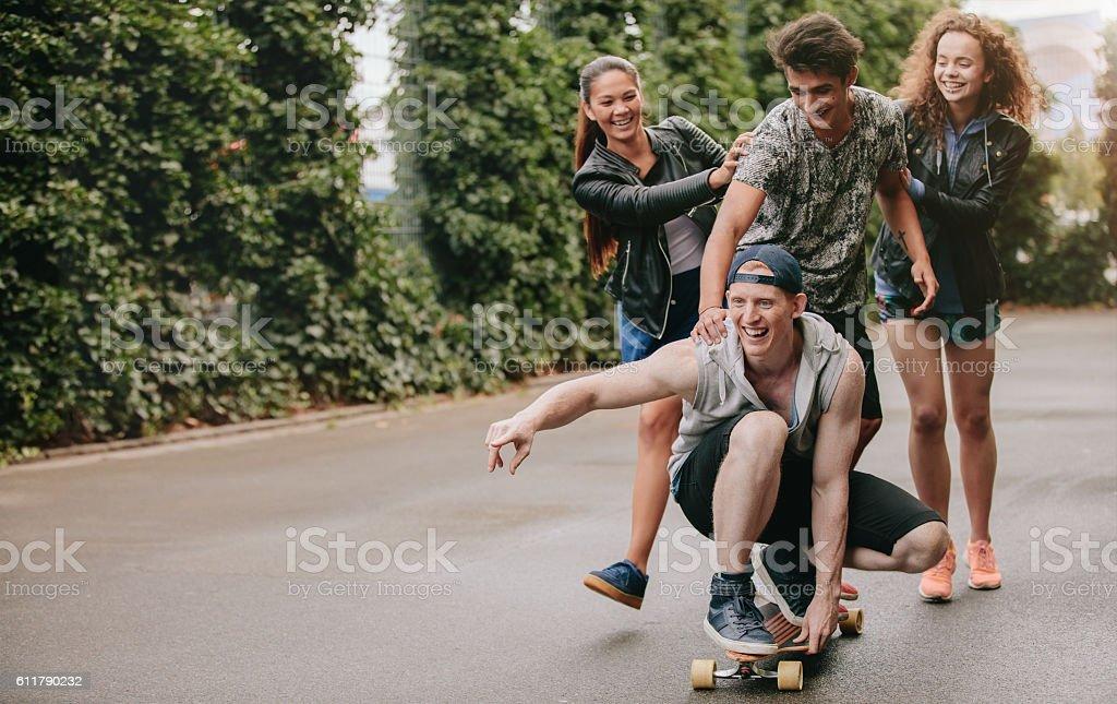 Group of friends having fun outdoors with skateboard stock photo