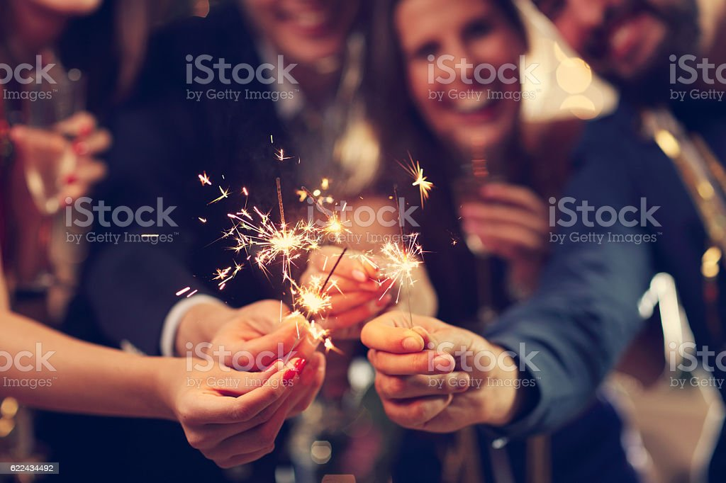 Group of friends having fun with sparklers stock photo