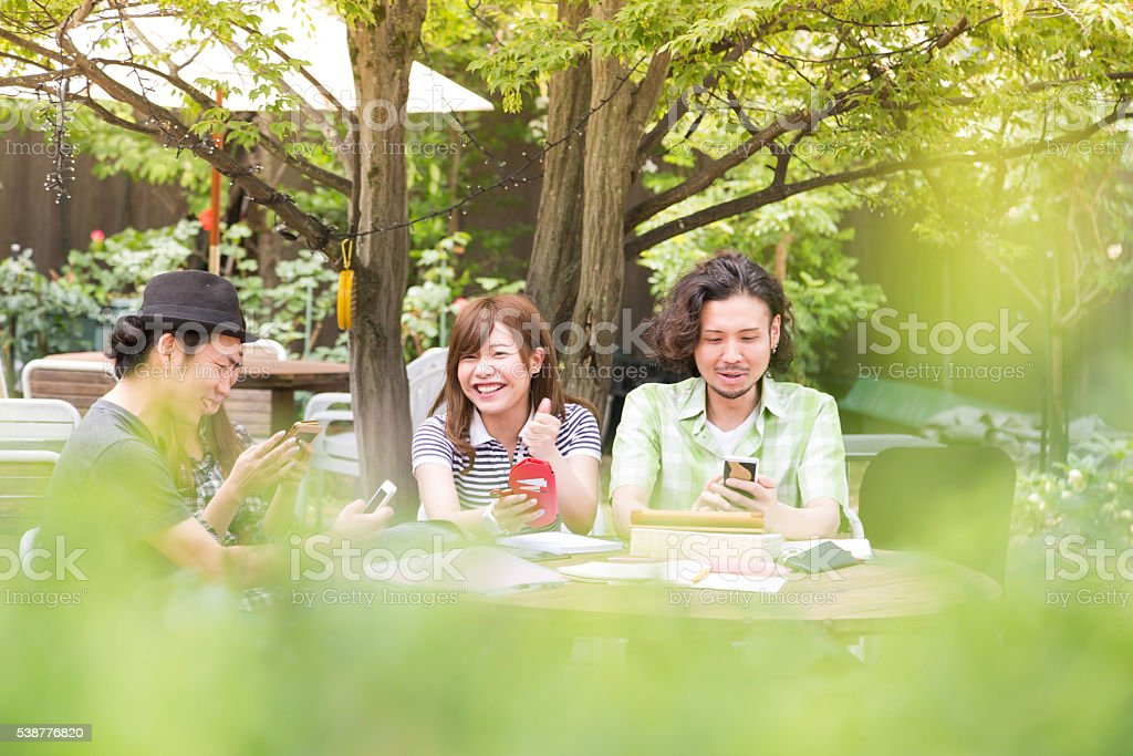 Group of friends having fun with their smartphones stock photo