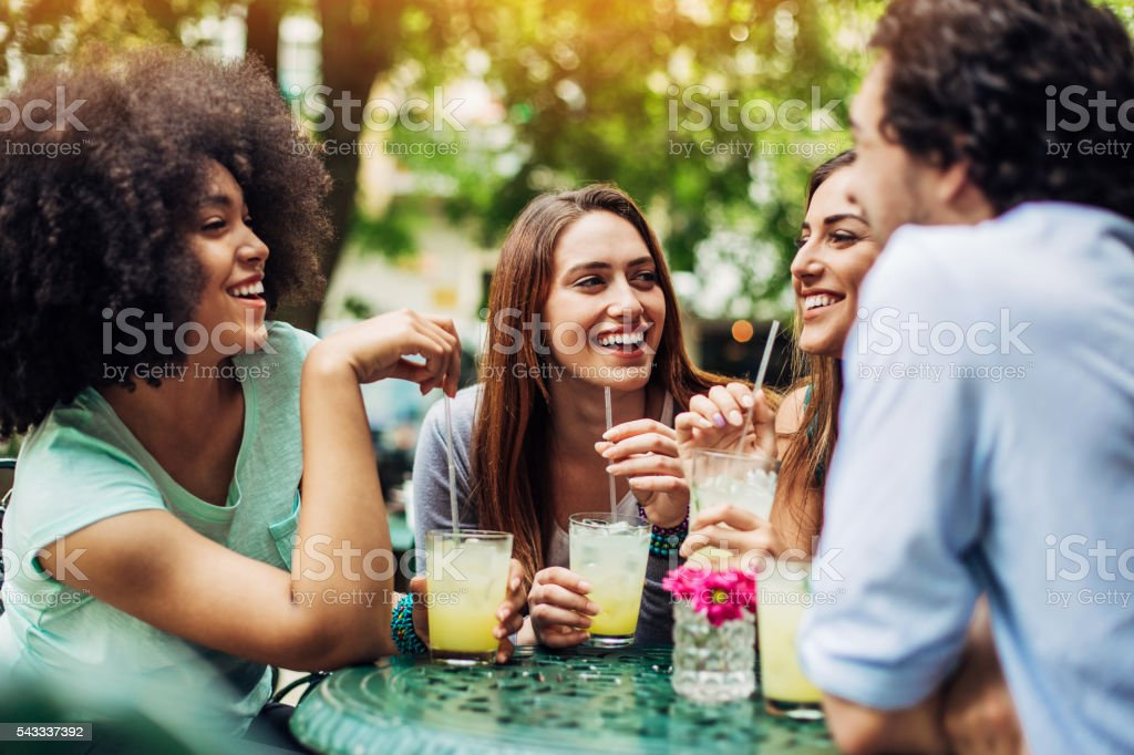 Group of friends having iced drinks in cafe stock photo