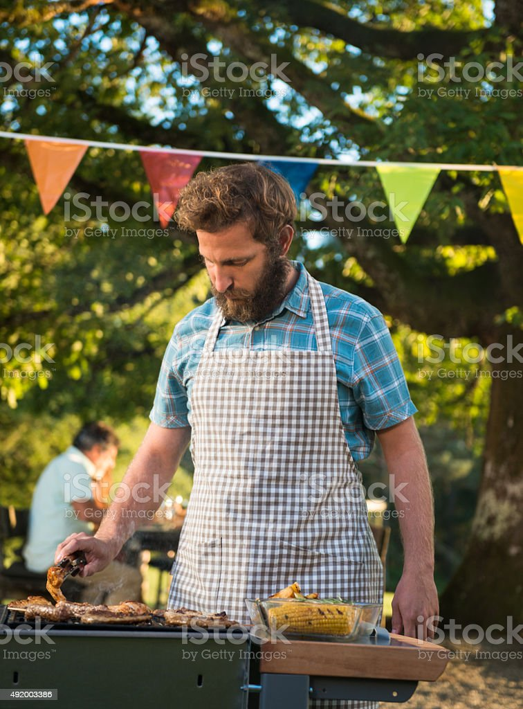 Group Of Friends Having Outdoor Barbeque stock photo