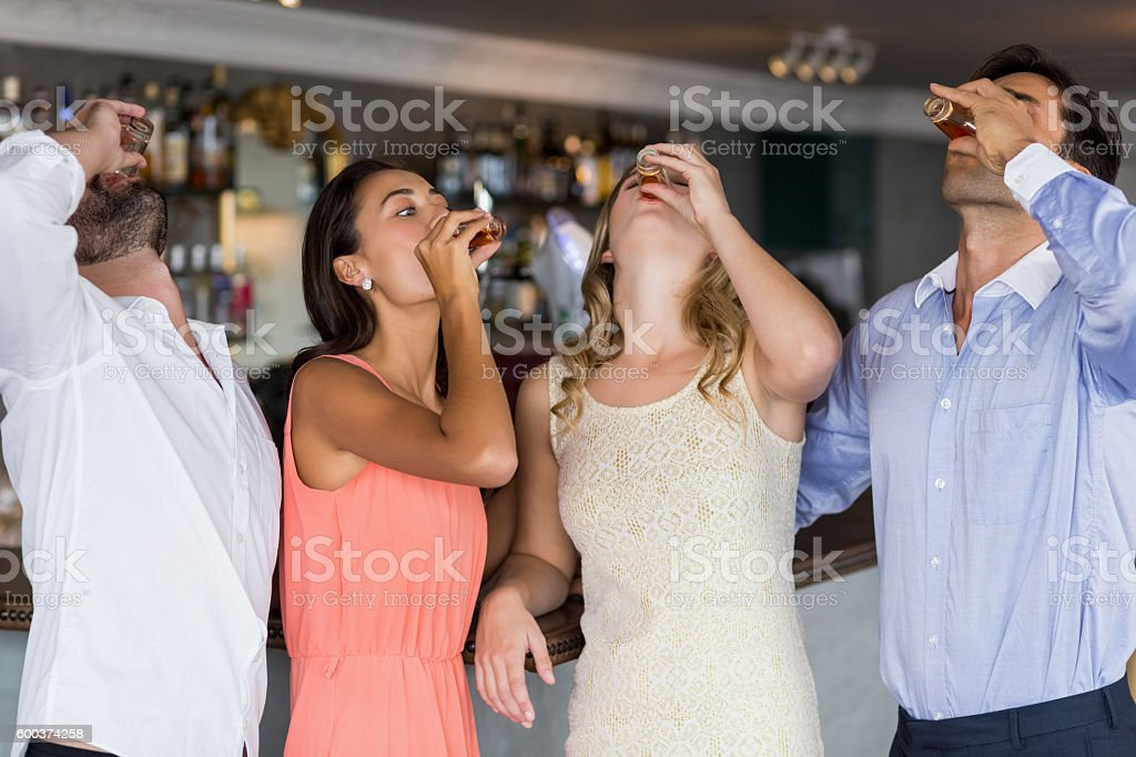 Group of friends having tequila shot stock photo