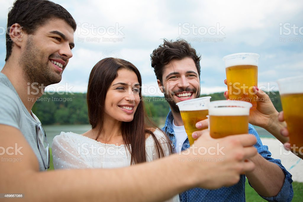 Group of friends holding beers and making a toast stock photo