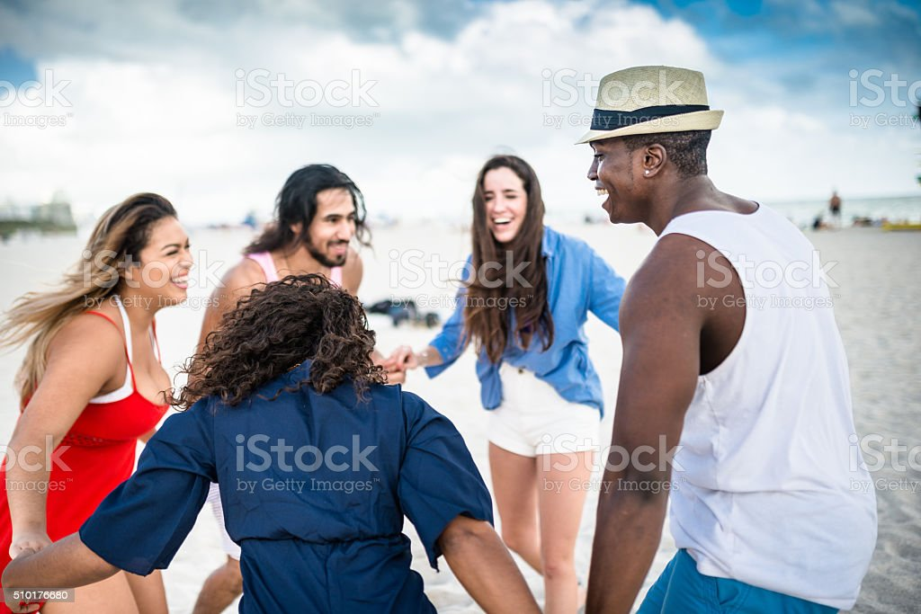 group of friends holding hands on the beach stock photo