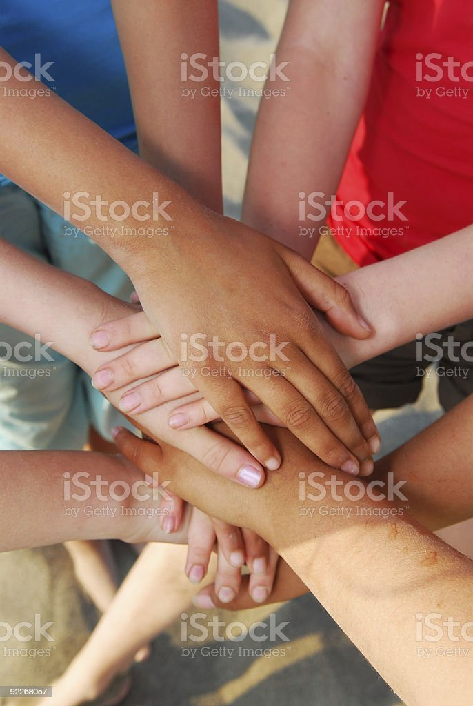 Group of friends holding hands showing team effort stock photo