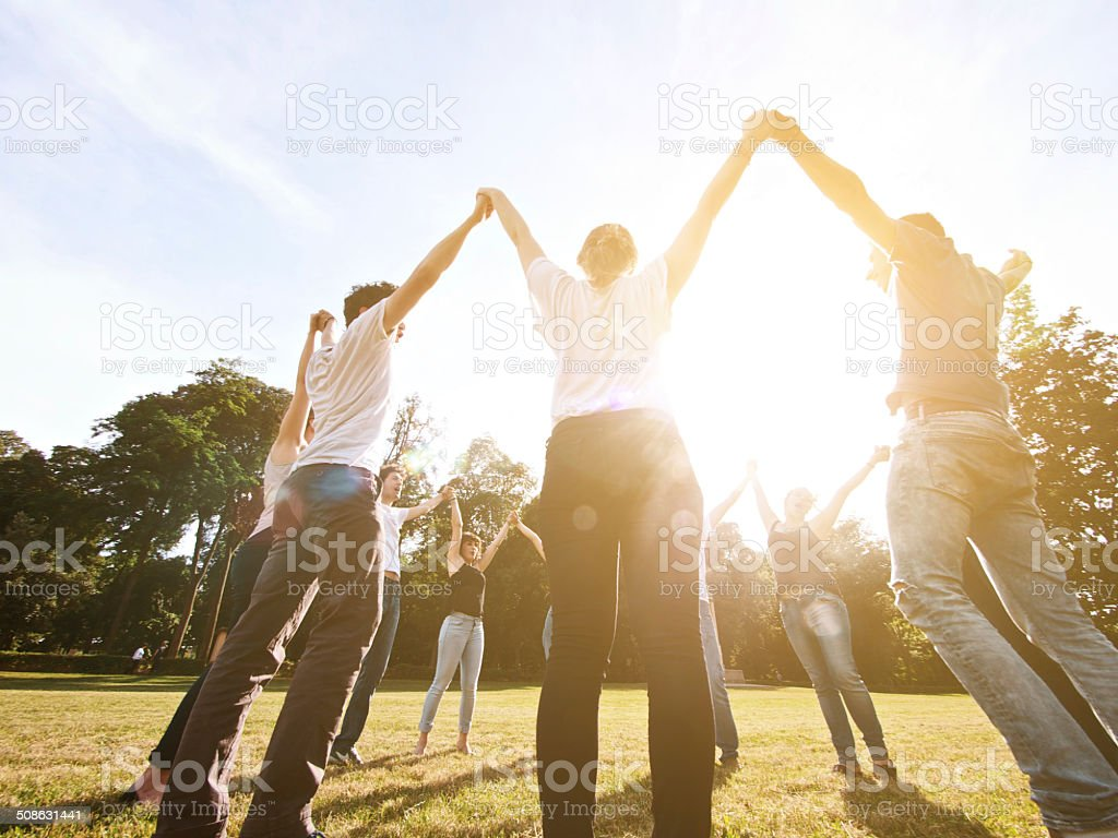Group of friends holding hands together making a circle stock photo