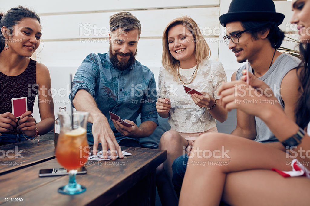 Group of friends in a party playing cards stock photo