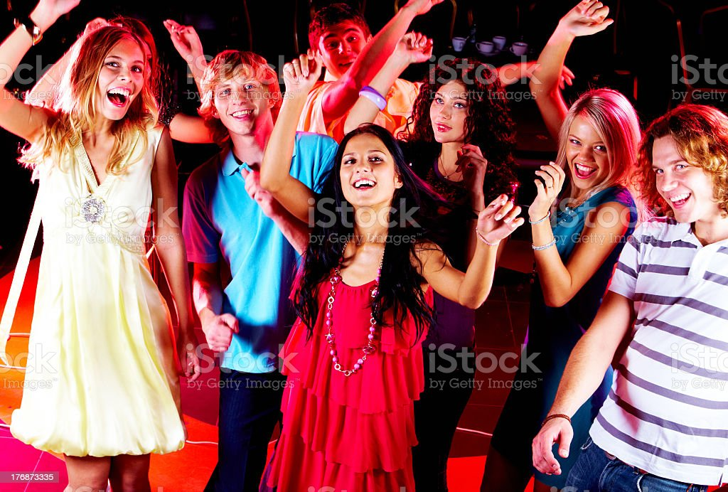 A group of friends in colorful attire dancing at a party royalty-free stock photo