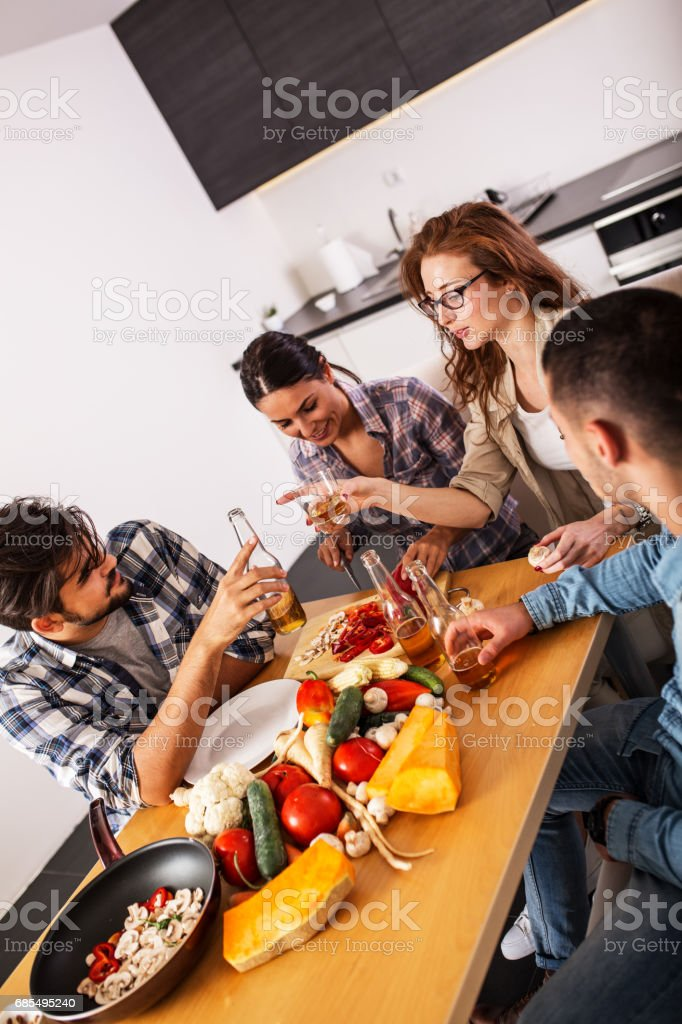 Group of friends in kitchen preparing together vegetarian meal. stock photo