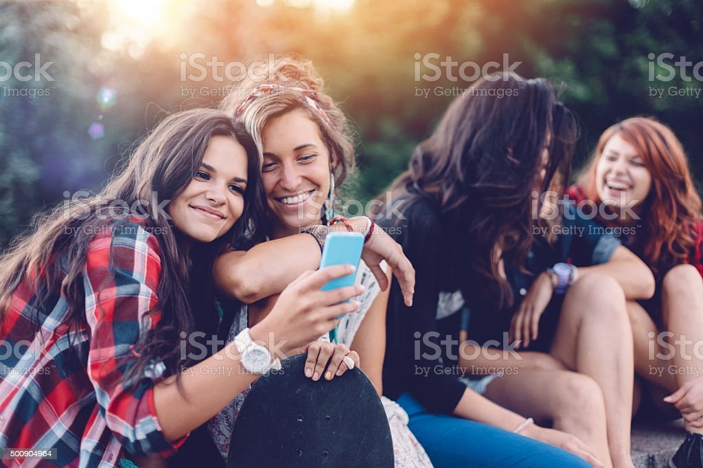 Group of friends in the park wasting time together stock photo