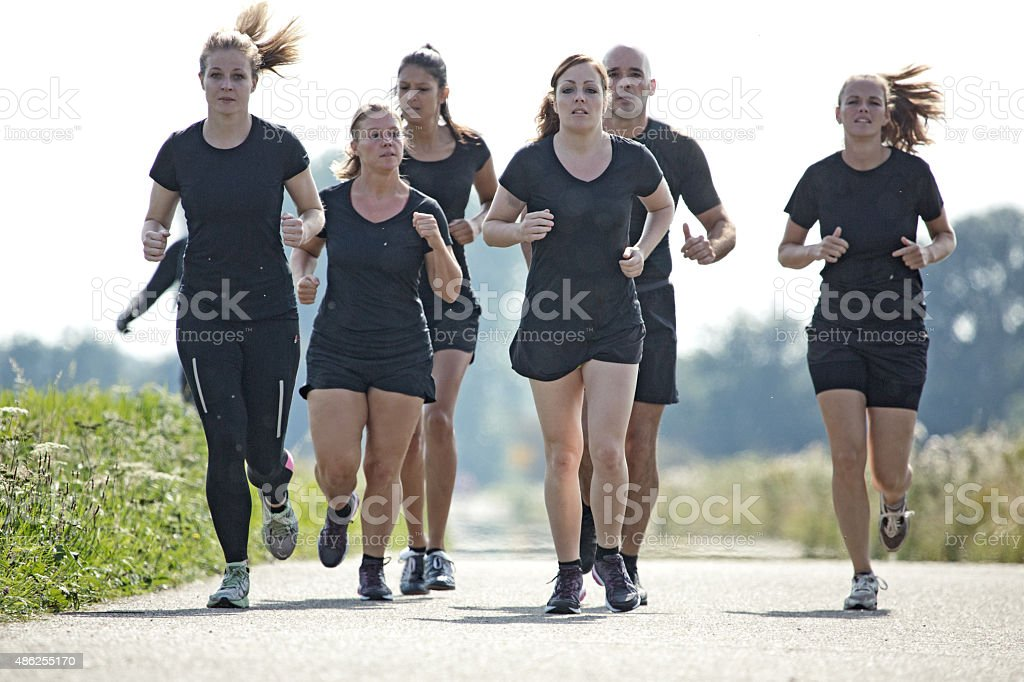 group of friends jogging outdoors stock photo