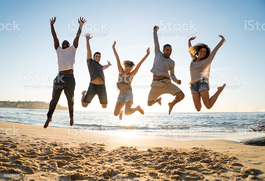 Group of friends jumping at the beach stock photo