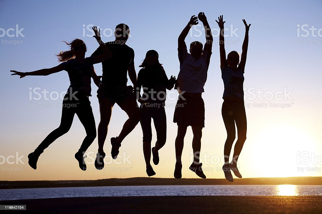 Group of friends jumping in front of a lake stock photo