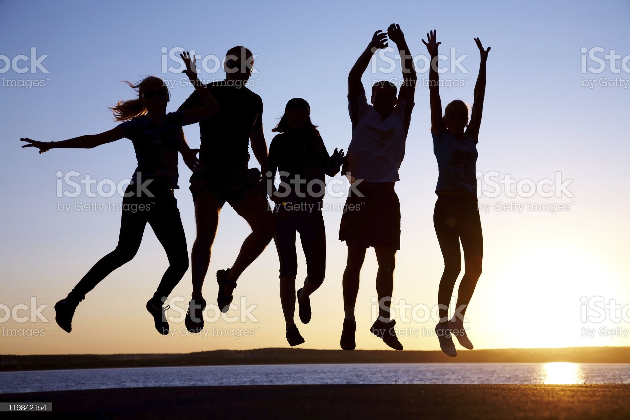 Group of friends jumping in front of a lake royalty-free stock photo
