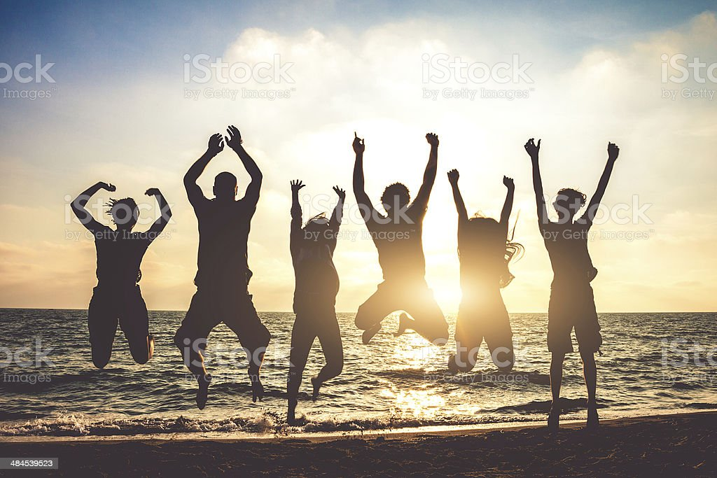 Group of friends jumping on the beach at dusk stock photo