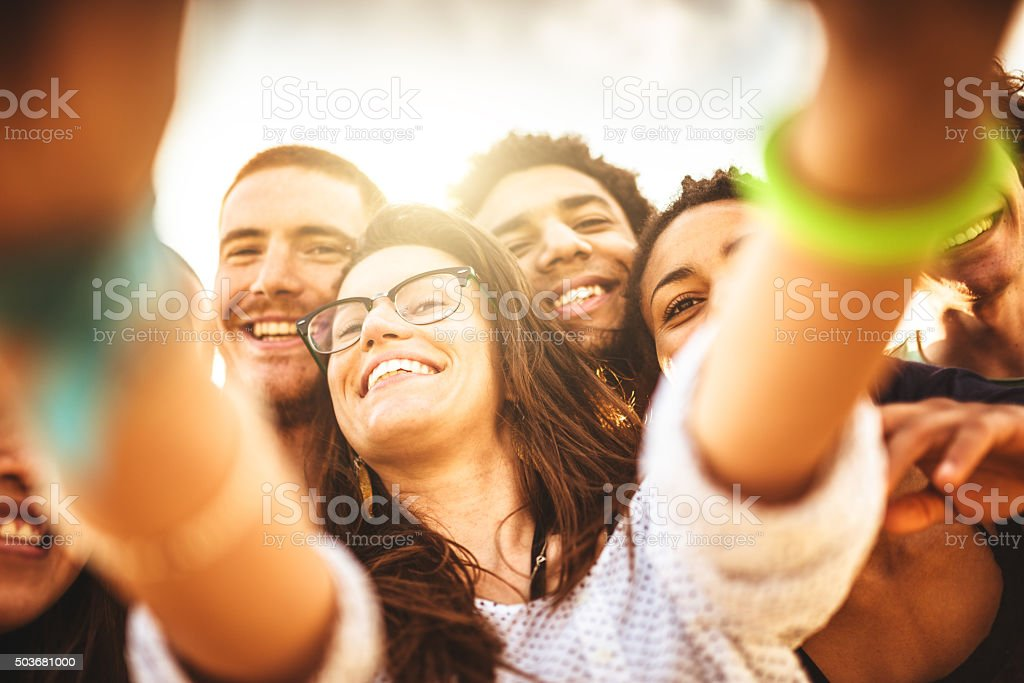 Group of friends laughing and doing a selfie stock photo