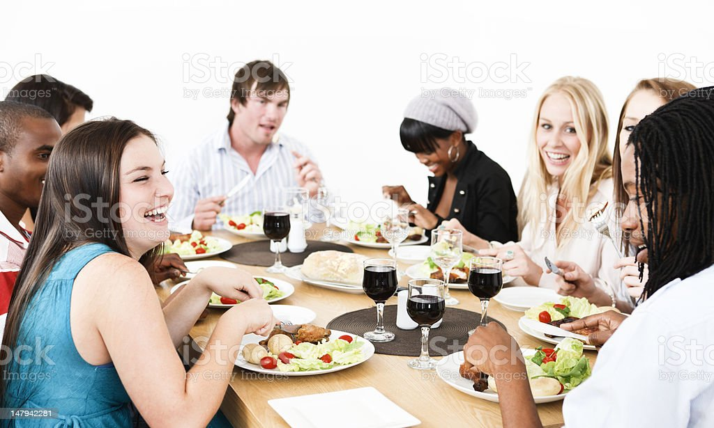 Group of friends laughing and eating dinner royalty-free stock photo