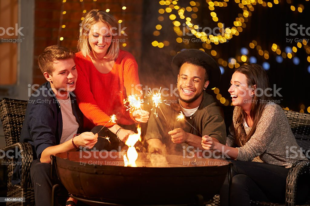 Group Of Friends Lighting Sparklers By Firepit stock photo