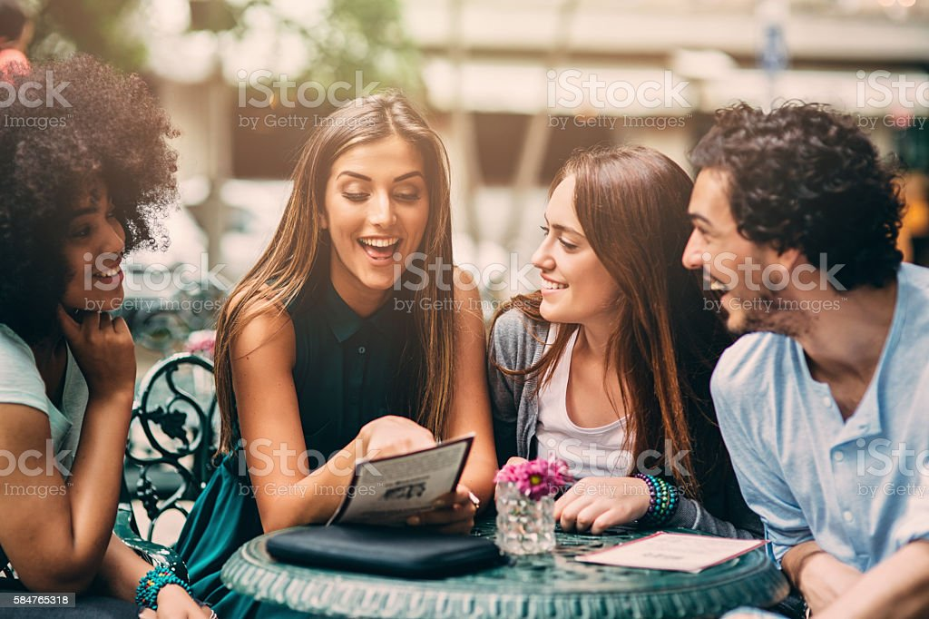 Group of friends looking at the menu stock photo