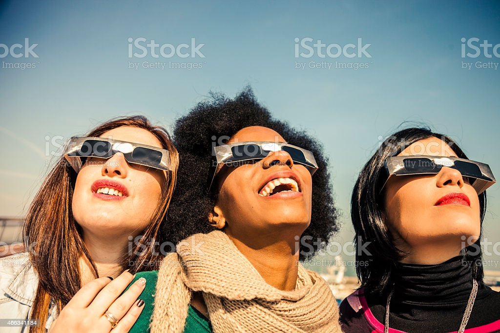 Group of friends looking to a solar eclipse stock photo
