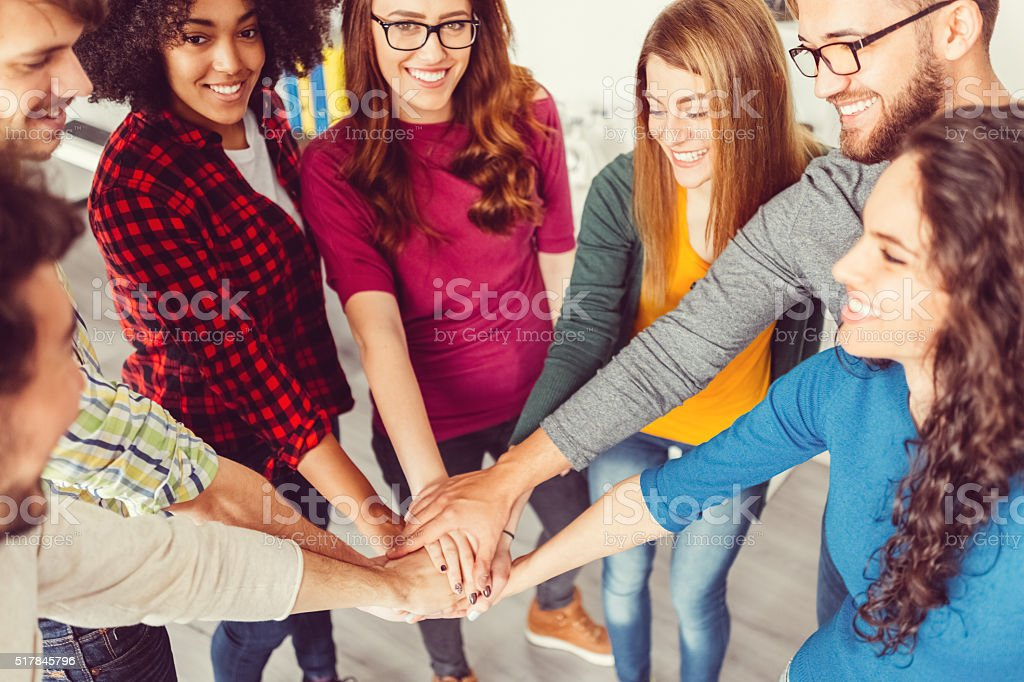Group of friends making a pile of hands stock photo