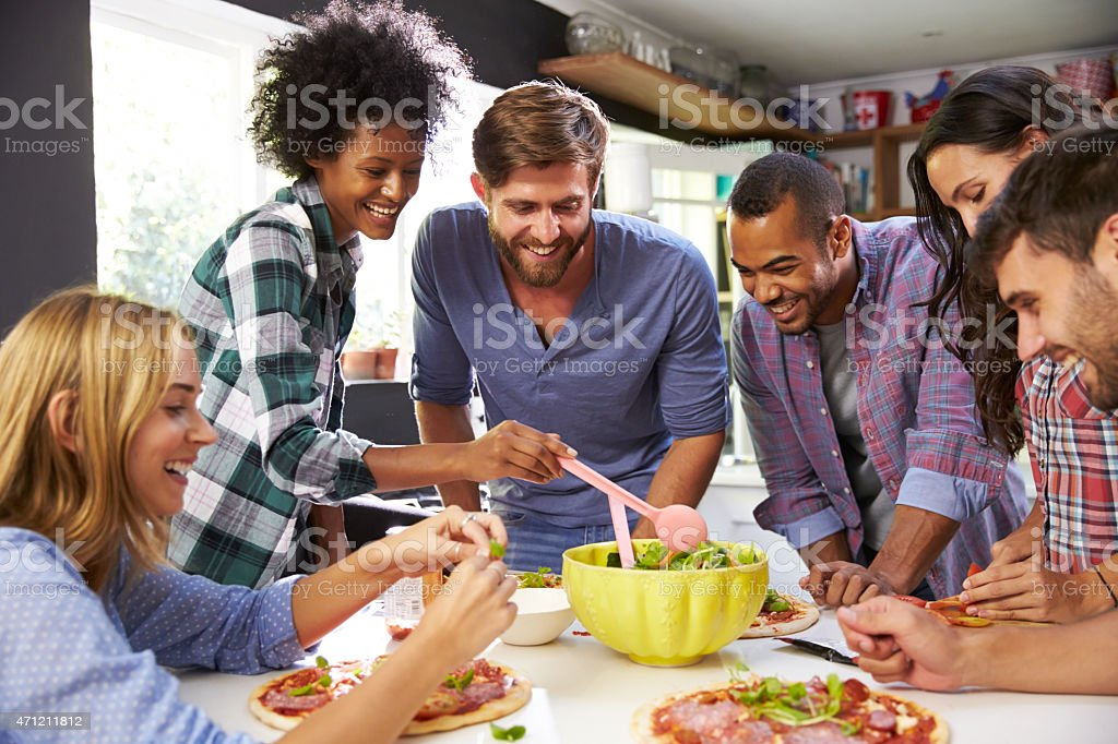 Group Of Friends Making Pizza In Kitchen Together stock photo