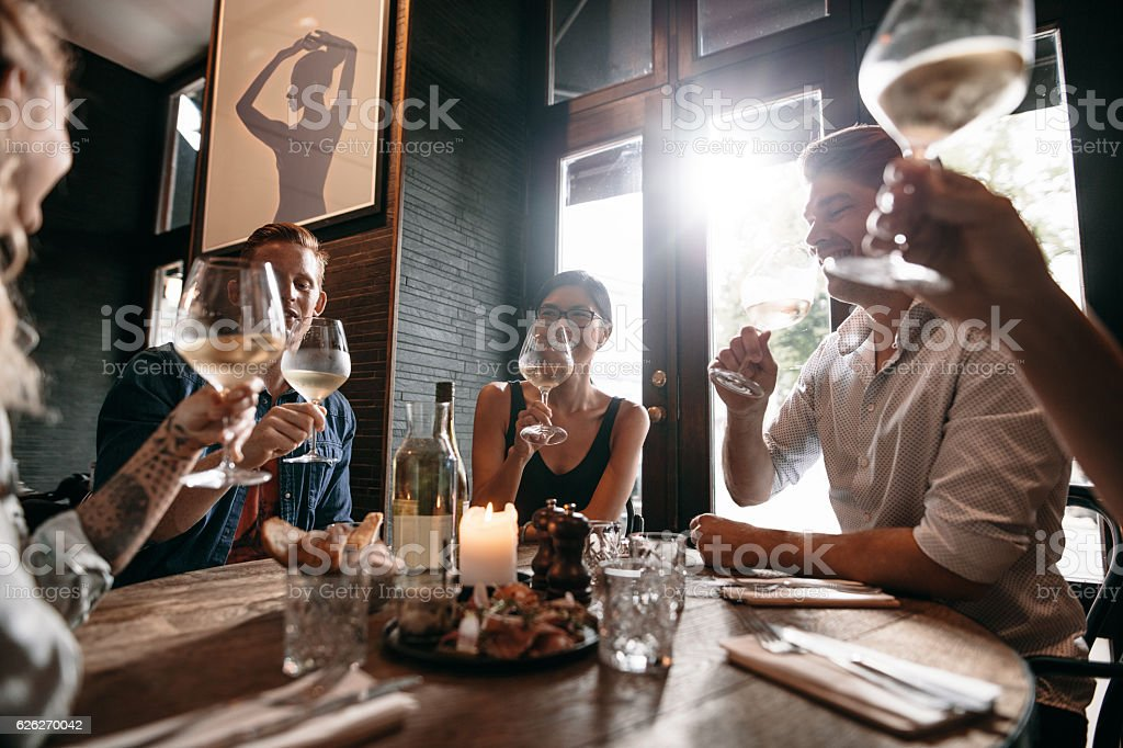 Group of friends meeting at a restaurant for dinner stock photo