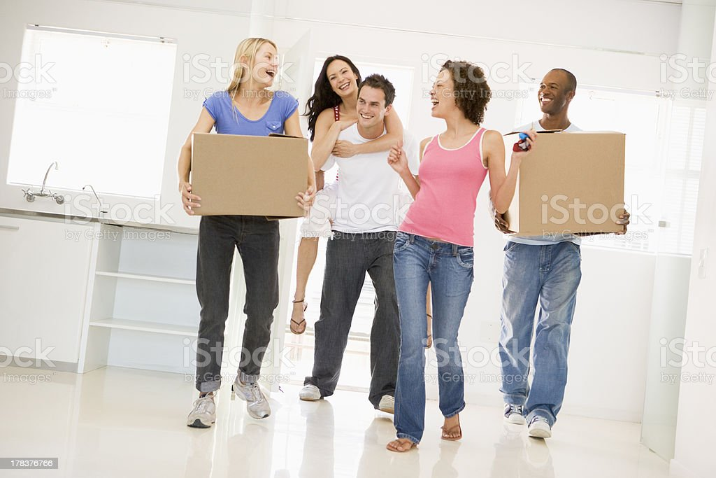 Group of friends moving into new home smiling stock photo