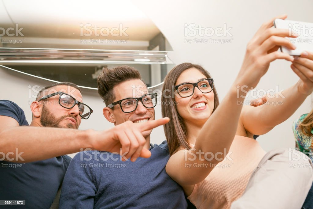 group of friends on couch takes a selfie stock photo