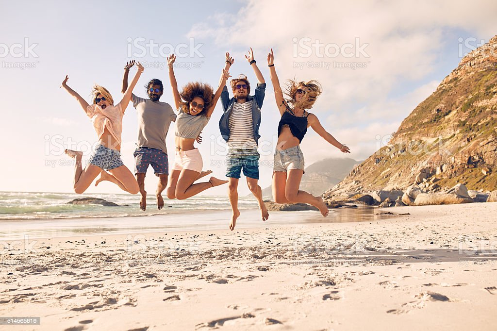 Group of friends on the beach having fun stock photo