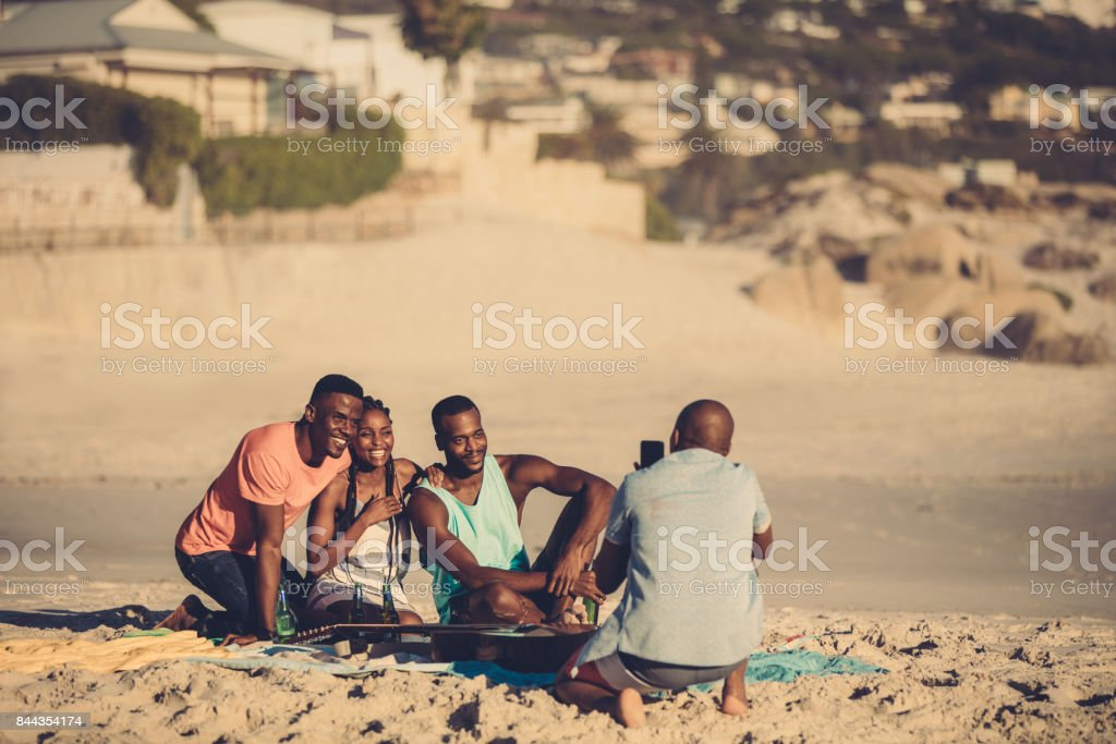 Group of friends on the beach taking pictures stock photo