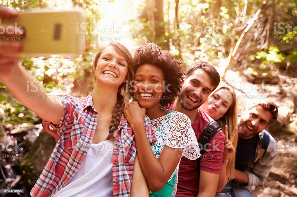 Group Of Friends On Walk Taking Selfie In Forest stock photo