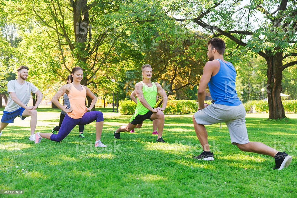group of friends or sportsmen exercising outdoors stock photo