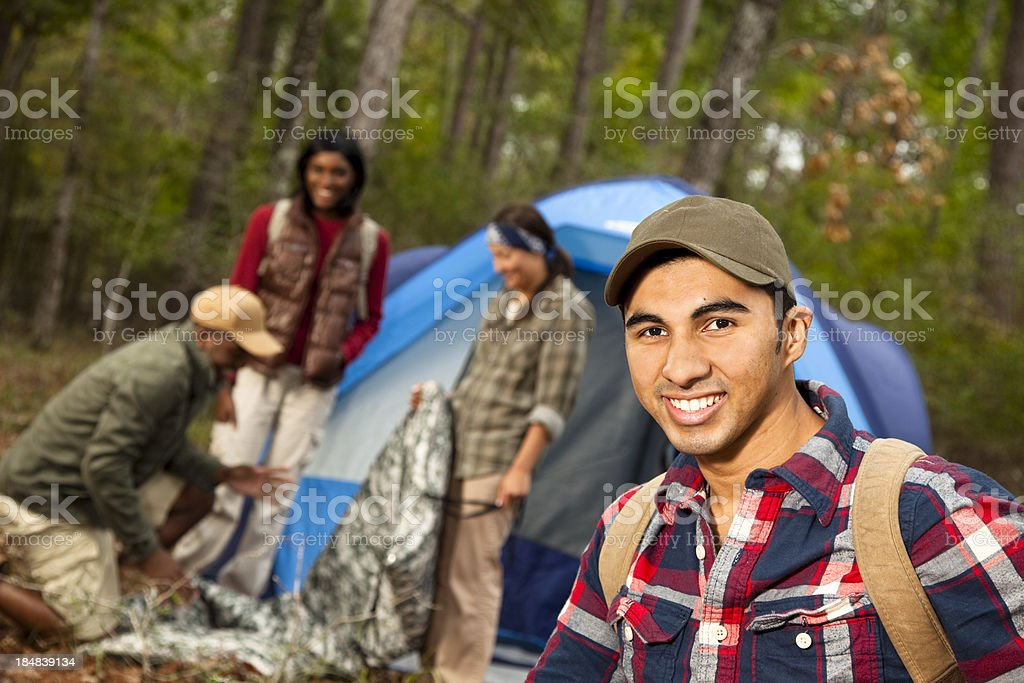 Group of friends outdoors camping. Tent. Latin man foreground. Forest. royalty-free stock photo
