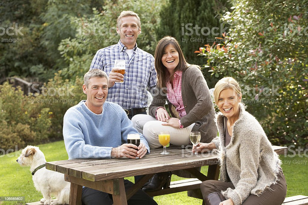 Group Of Friends Outdoors Enjoying Drink In Pub Garden royalty-free stock photo