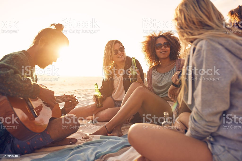 Group of friends partying on the beach at sunset stock photo