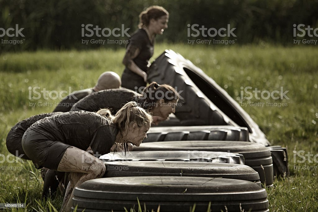 group of friends picking up tyres during mud run stock photo