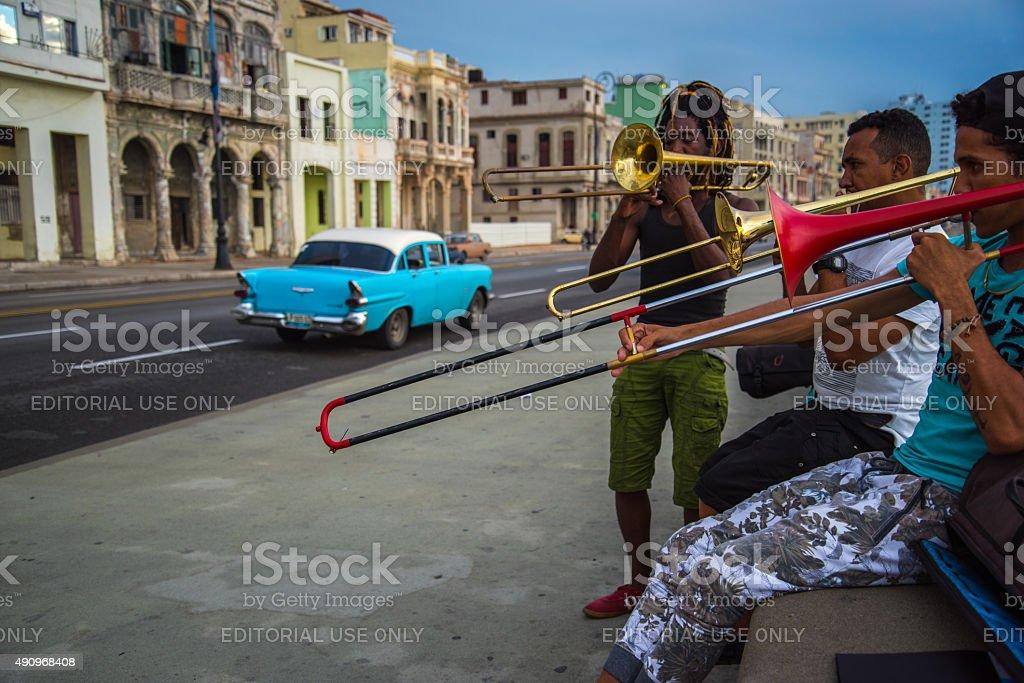 Group of friends play music on Malecon in Havana,Cuba. stock photo