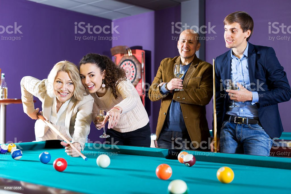 Group of friends playing billiards stock photo