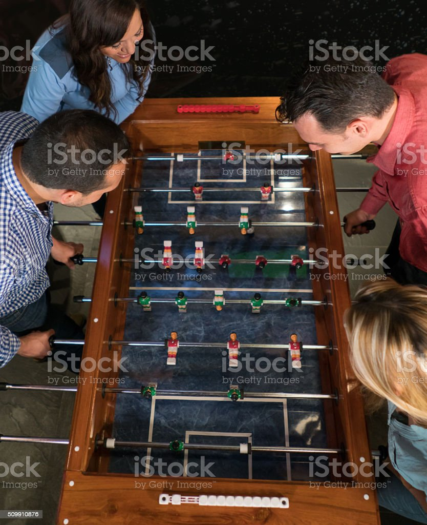 Group of friends playing foosball at a bar stock photo