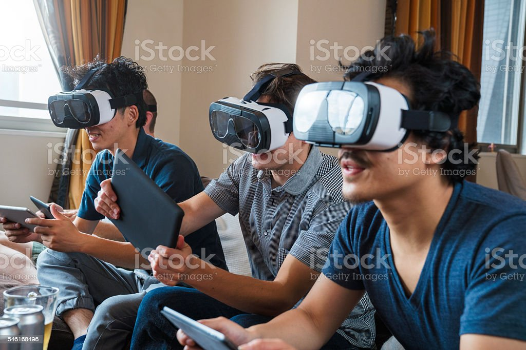 Group of friends playing games using virtual reality headsets stock photo
