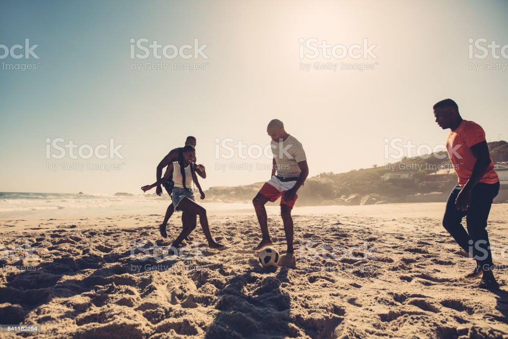Group of friends playing soccer on the beach stock photo