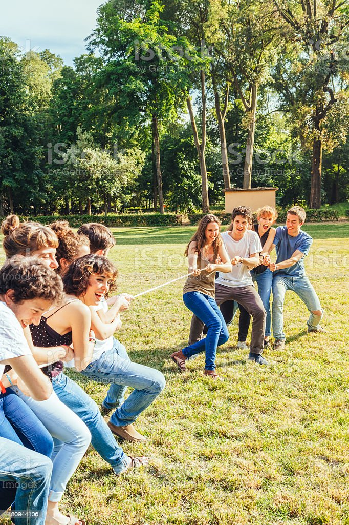 Group of friends playing tug of rope in park stock photo