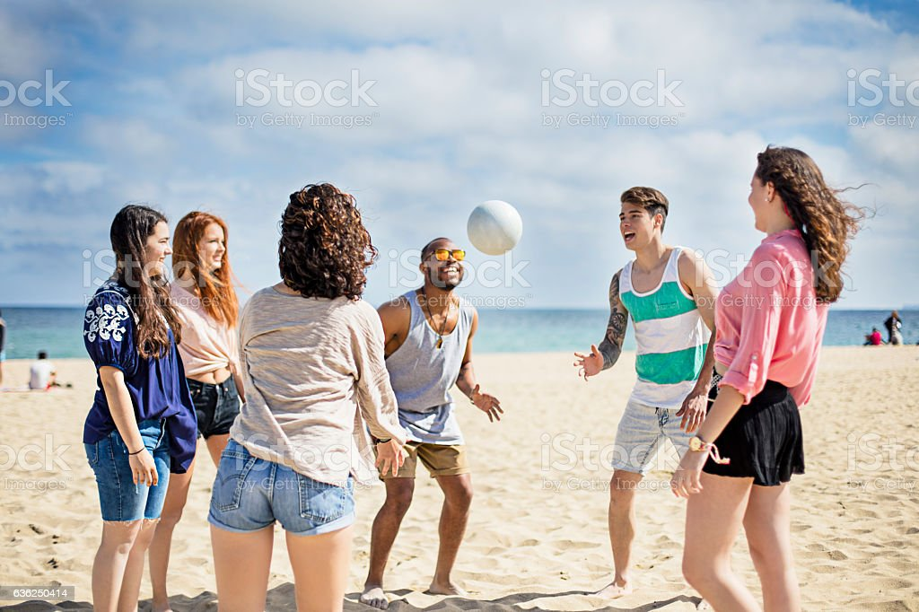 Group of friends playing volley ball on the beach stock photo