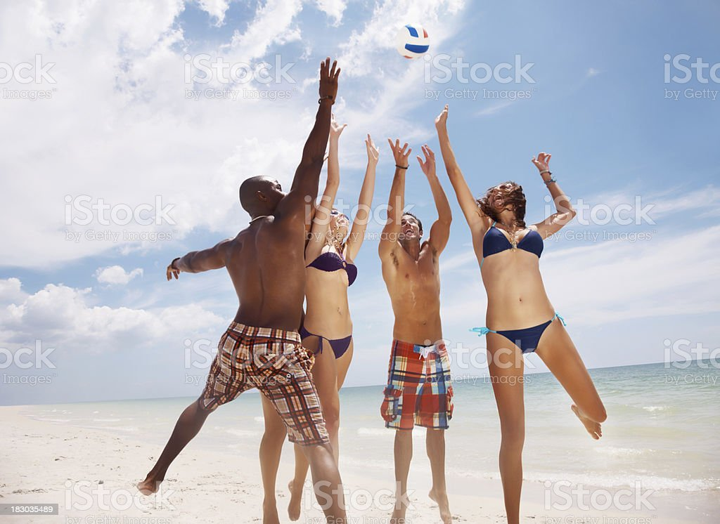 Group of friends playing volleyball on beach against sky royalty-free stock photo