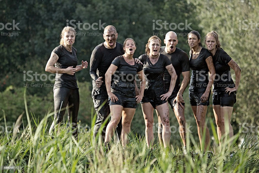 group of friends posing on hill during obstacle run stock photo