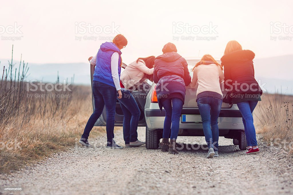 Group of friends pushing car on the rural road stock photo